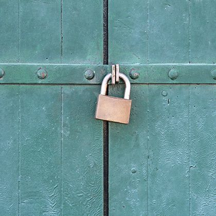 padlock hanging from turquoise painted wooden doors